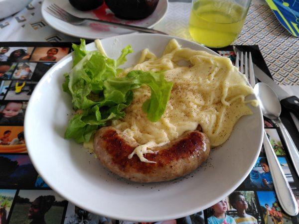 assiette contenant une feuille de salade, des saucisses juteuses et bien grillées ainsi que de l'aligot bien sûr