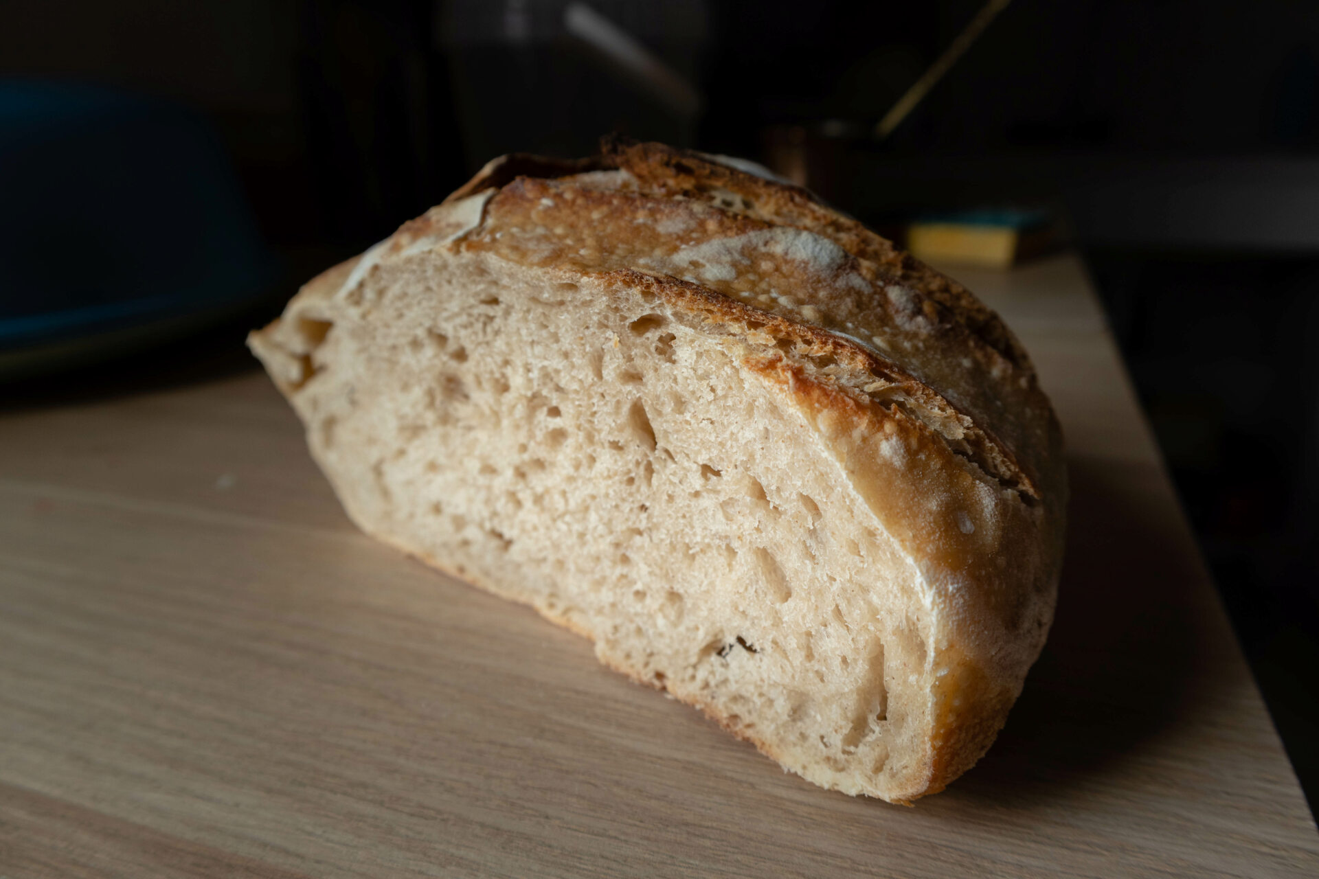 photographie d'un pain au levain à la croûte bien dorée et à la mie aérée, grâce au travail du levain