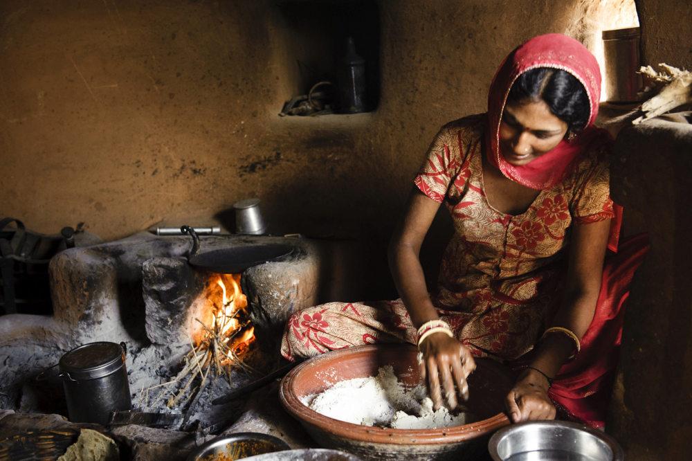 femme préparant des chapatis traditionnellement cuits au feu de bois en Inde
