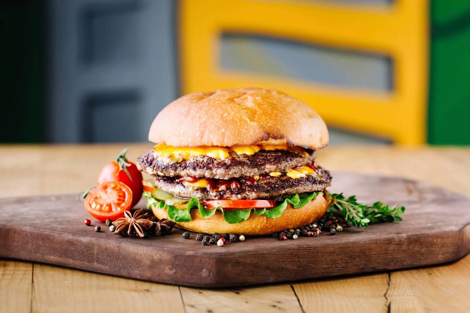 photo d'un double cheeseburger fait maison, posé sur une épaisse planche à découper en bois